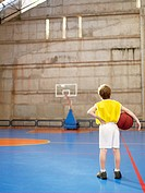 Boy looking at basketball hoop rear view