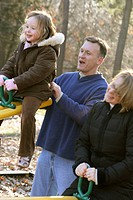 family having fun on a see-saw in a park