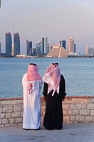 Two men wearing traditional dress of thobe and gutra headdress looking across Doha Bay from the Corniche to the new city skyline and West Bay business...