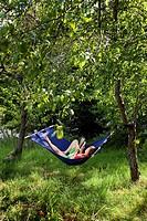 Woman lying on hammock with reading newspaper En kvinna med röd bikini och gröna shorts ligger i en blå hängmatta och läser en tidning i en grön solig...