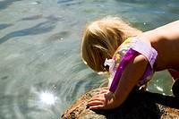 Boy sitting by lake Ett barn med simpuff känner på solbelyst vatten stödd mot en klippa.