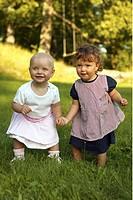 Twins playing at garden Två små barn, flickor, leker och håller varandra i handen, utomhus i gräset en solig sommardag. Foto: Paulian Westerlind Kod: ...