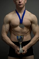 A muscular man clutching trophy and wearing medal