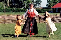 Kvinna iförd folkdräkt dansar med två flickor på midsommar. Senior Woman With Traditional Costume Dancing With Two Girls, Midsummer, Sweden