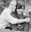 Mother and daughter 16_17 years, portrait b/w Två unga kvinnor som håller om varandra ler och tittar in i kameran.