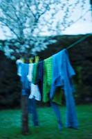 En Tvättlina Med Tvätt Utomhus I En Trädgård Framför Ett Blommande Träd I Skymningen, Laundry Drying On String In Garden