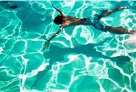 Man in swimming pool, floating on water Bada i en uppvärmd pool