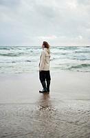 En Kvinna Står På En Strand Och Tittar Ut Över Havet, Mature Woman Standing At Beach