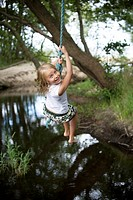 Flicka svingar sig i rep över vatten. Girl Swinging In Rope Over Pond.