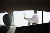 Man holding map outside car