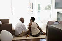 Couple sitting on living room floor