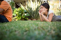 Girl and boy relaxing in grass