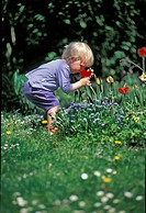 Little boy to takes a smell at a tulip in the garden