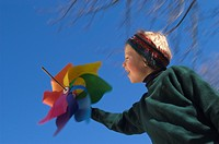 Eight year old boy palying with colorful wind wheel MR