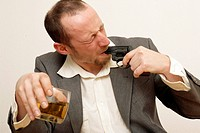Sad man shoots in his mouth holding a whiskey glas