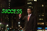 Businessman writing success in green