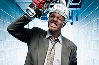 Grimacing businessman in a sports helmet