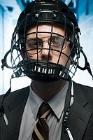 Injured businessman wearing an ice hockey helmet