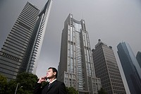Businessman near skyscrapers