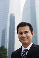 Smiling businessman near skyscrapers