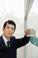 Japanese businessman leaning on a window