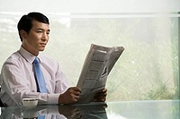 Chinese businessman reading a newspaper