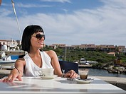 Young woman having coffee by harbour