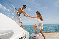 Young man helping girlfriend onto catamaran