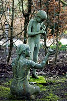 Garden ornaments. Sculptures of a woman and a boy. Photographed at the RHS Royal Horticultural Society garden in Rosemoor, Devon, UK.