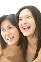 Mature woman and young woman smiling, white background