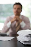 Businessman sitting at desk in office, pile of envelopes in foreground, front view, differential focus