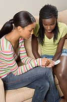 South African teen culture _ Two young woman discussing the contraceptive pill.