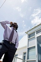 Low angle view of a businessman talking on his mobile phone, Cape Town, Western Cape Province, South Africa