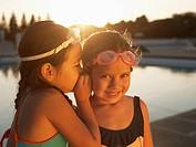 Girls sharing secret by swimming pool