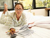 Young woman counting bills on bed