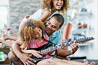 Father and Daughters Playing Guitar