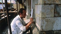 Conservationist cleaning and repairing stone work in Old Cloth Hall after effects of Acid rain. Kracow. Poland