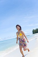 Portrait of a young woman running on beach, smiling, Saipan, USA