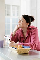 Mid adult woman with newspaper at kitchen counter