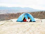 Couple in tent, rock strata in background, Moab, Utah, USA