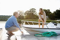 Couple untying motorboat from dock