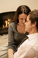 Mid adult couple hugging by fireplace