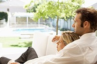 Mid adult couple relaxing on sofa and looking at garden (thumbnail)