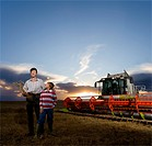 Farmer and son standing next to combine harvester in wheat field