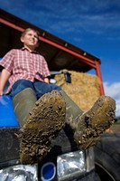 Boy sitting on tractor with muddy boots