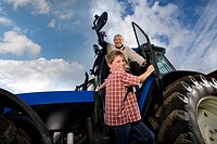 Portrait of smiling farmer and grandson leaning out of tractor