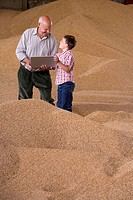Farmer and grandson holding laptop on wheat grain heap