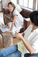 Young couple in living room, woman using laptop