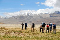 Trekking group passes wide river plain with snow capped mountains in the background near Lungchang Tibet China