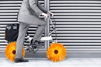 Businessman riding bike with flower wheels